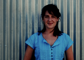 clare_armitage_blue_shirt_corrugated_metal_background.png