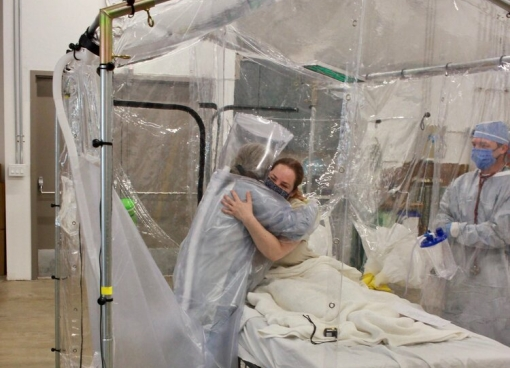 A patient in bed receiving a hug from a clinician in the Care Cube, an airborne infection isolation tent