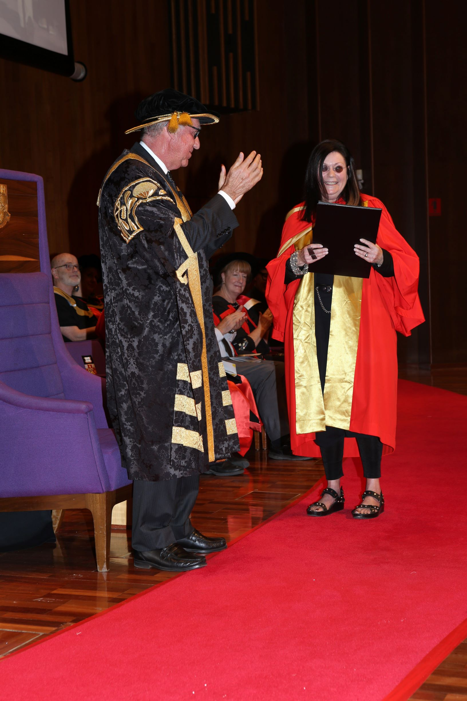 Dr Gene Sherman AM receives her degree from UNSW Chancellor David Gonski AC