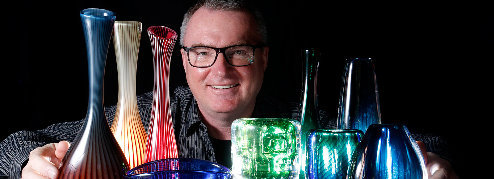 Mark Ian Jones with part of his Vicke Lindstrand glass collection. Photo: Grant Turner/Mediakoo